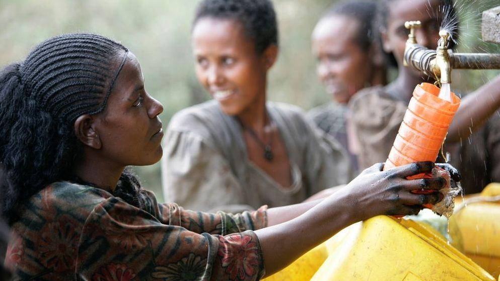 Frauen in Afrika befüllen Wasserkanister an einem von der UNICEF errichteten Brunnen.