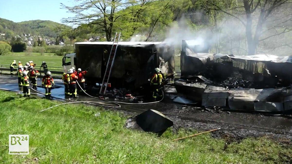 Feuerwehrleute löschen einen in Brand geratenen Lastwagen, dessen Anhänger komplett zerstört wurde.