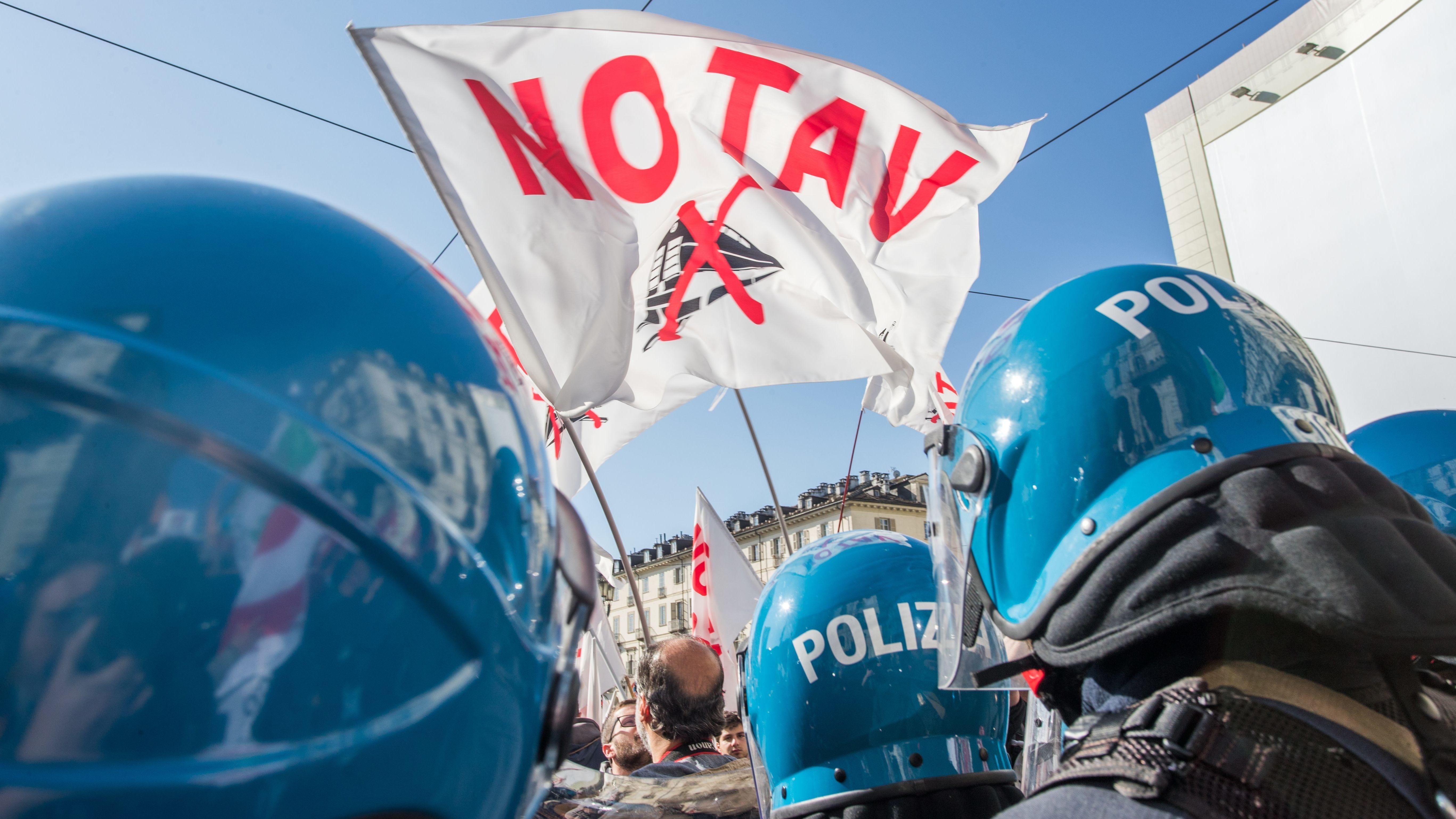 Gegner des TAV halten bei einer Demonstration eine No-TAV-Fahne hoch. Polizisten mit blauen Helmen stehen ihnen gegenüber.