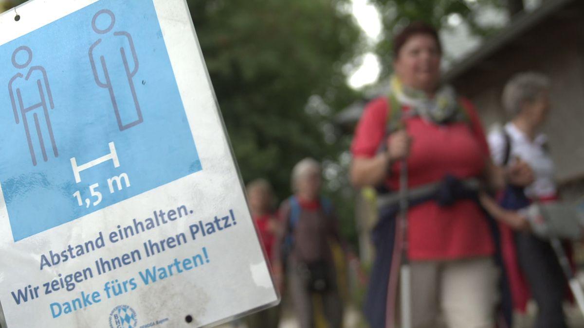 """Pilgergruppe auf dem Weg zum Kloster Banz. Im Vordergrund eine Tafel mit der Aufschrift: """"Abstand einhalten. Wir zeigen Ihnen Ihren Platz! Danke fürs Warten!"""""""