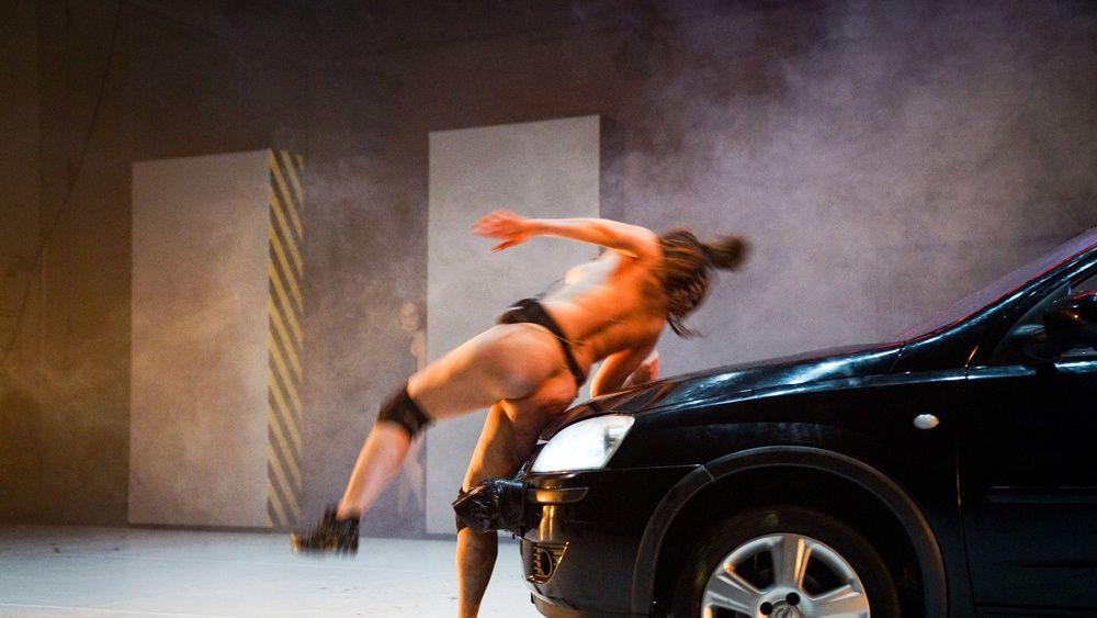 Das Foto zeigt eine nackte Schauspielerin, bekleidet nur mit Schuhen und Knieschonern, die scheinbar von einem Auto angefahren wird.