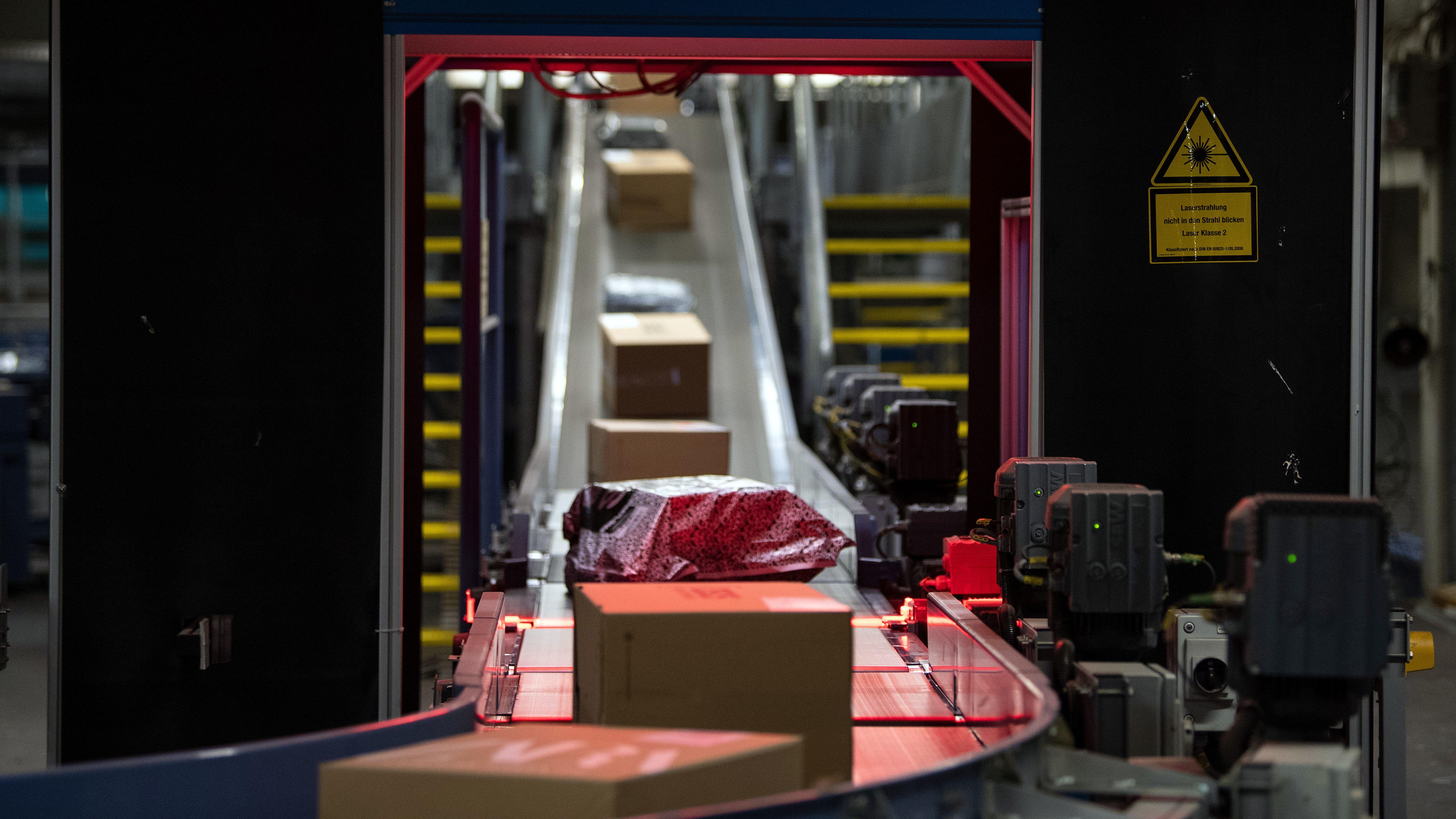 Zahlreiche Pakete fahren auf einem Förderband unter einem Scanner
