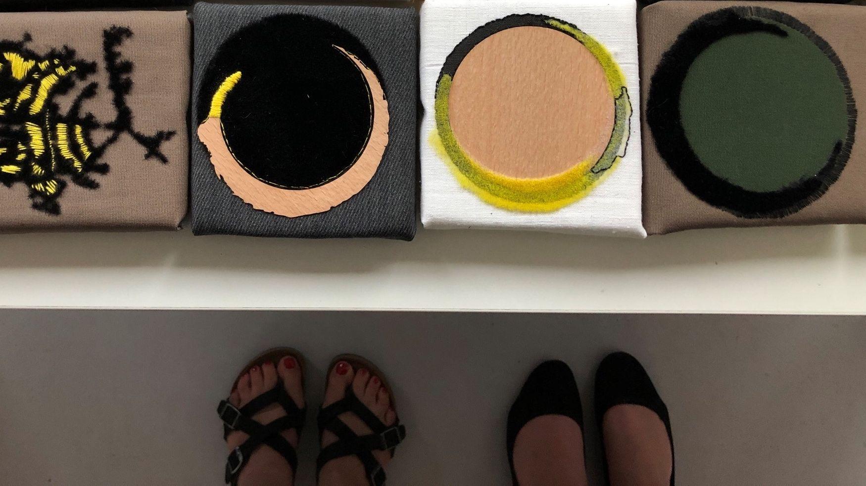 Füße in Sommerschuhen stehen vor einem Kunstwerk