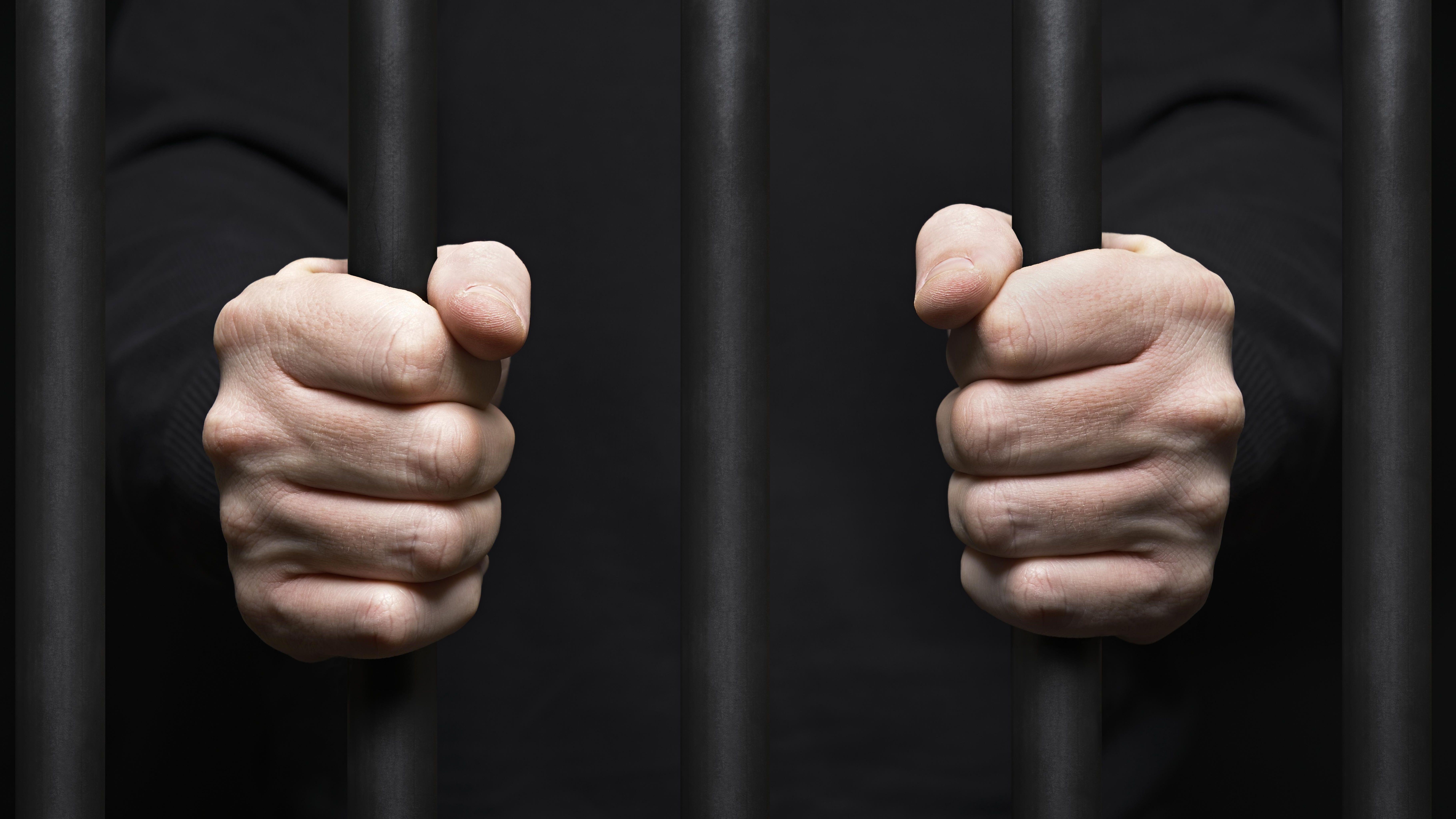Häftling umklammert Gitterstäbe