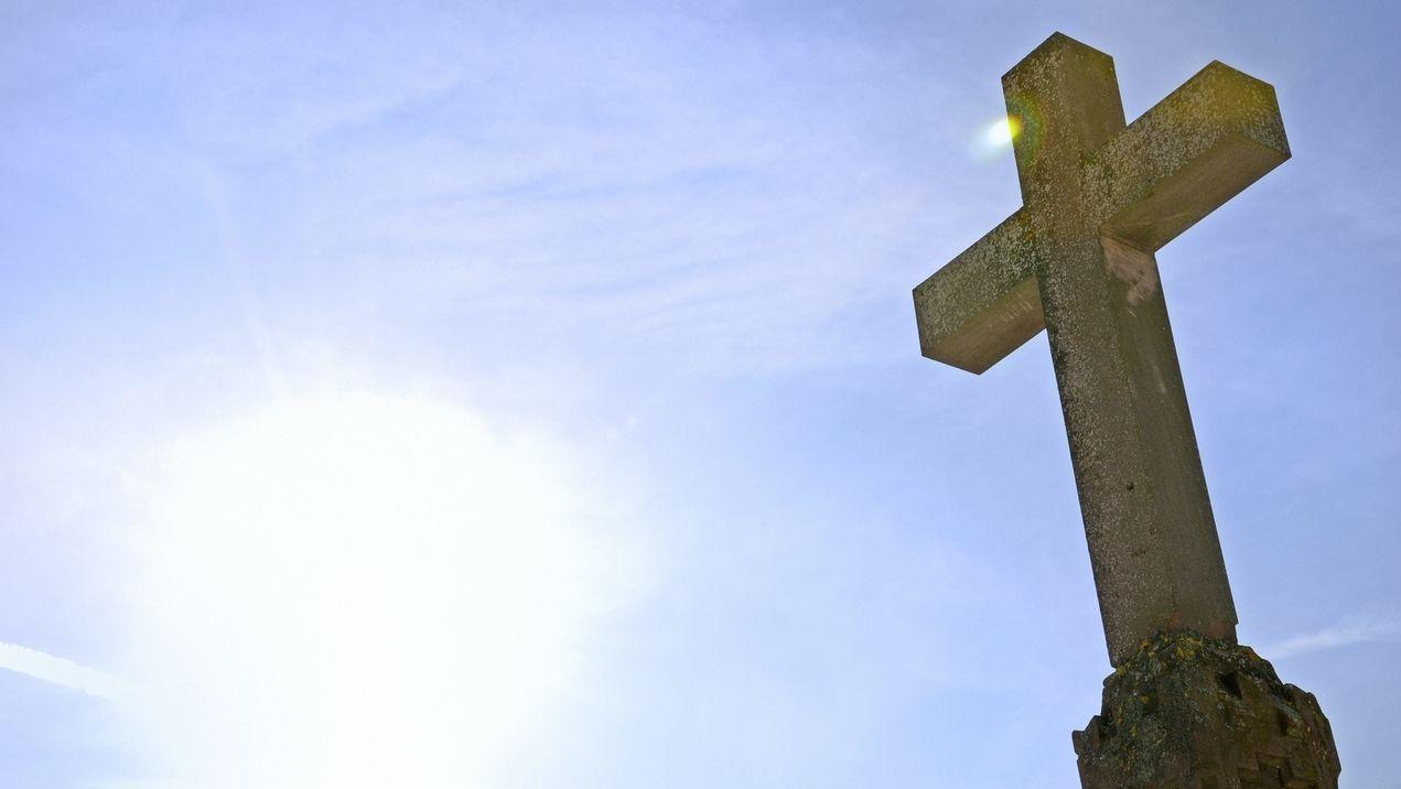 Ein Steinkreuz vor blauem Himmel (Symbol)