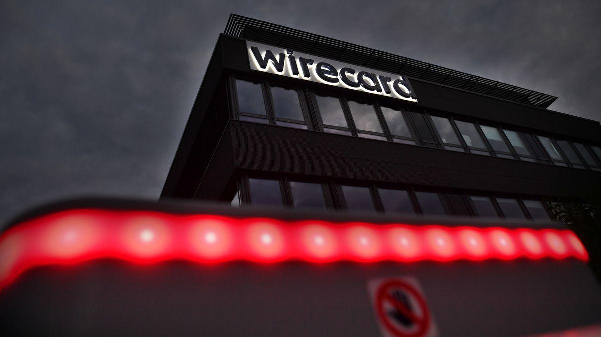 Der Schriftzug Wirecard leuchtet an der Fassasde des Firmensitzes. Darunter ein rotes Lichtband und ein Stoppzeichen.