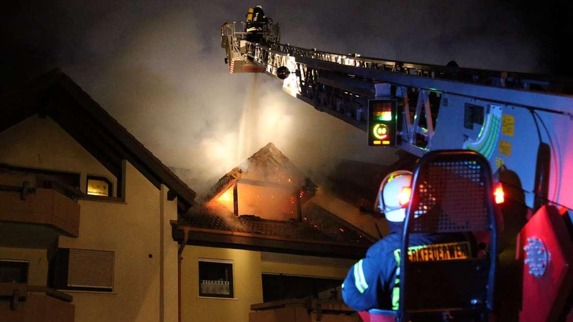 Ein Feuerwehrmann löscht von oben aus der Drehleiter den Brand im Dachgeschoss eines Hauses