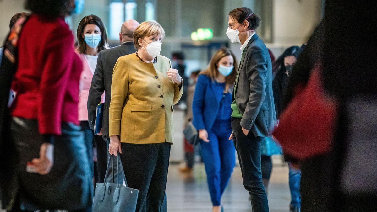 Bundeskanzlerin Angela Merkel (CDU) spricht nach der Debatte beim Bund-Länder-Gipfel mit Karl Lauterbach, SPD-Gesundheitsexperte