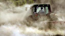 Ein Landwirt bearbeitet ein trockenes Feld mit einer Egge. | Bild:picture-alliance/dpa