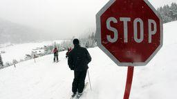 Skifahrer bei einem Stoppschild auf einer Skipiste.  | Bild:pa/dpa/Lukas Barth