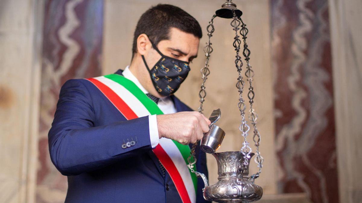 Pathetisches Gedenken: Der Politiker mit einem Kännchen in der Hand an einem Ölgefäß