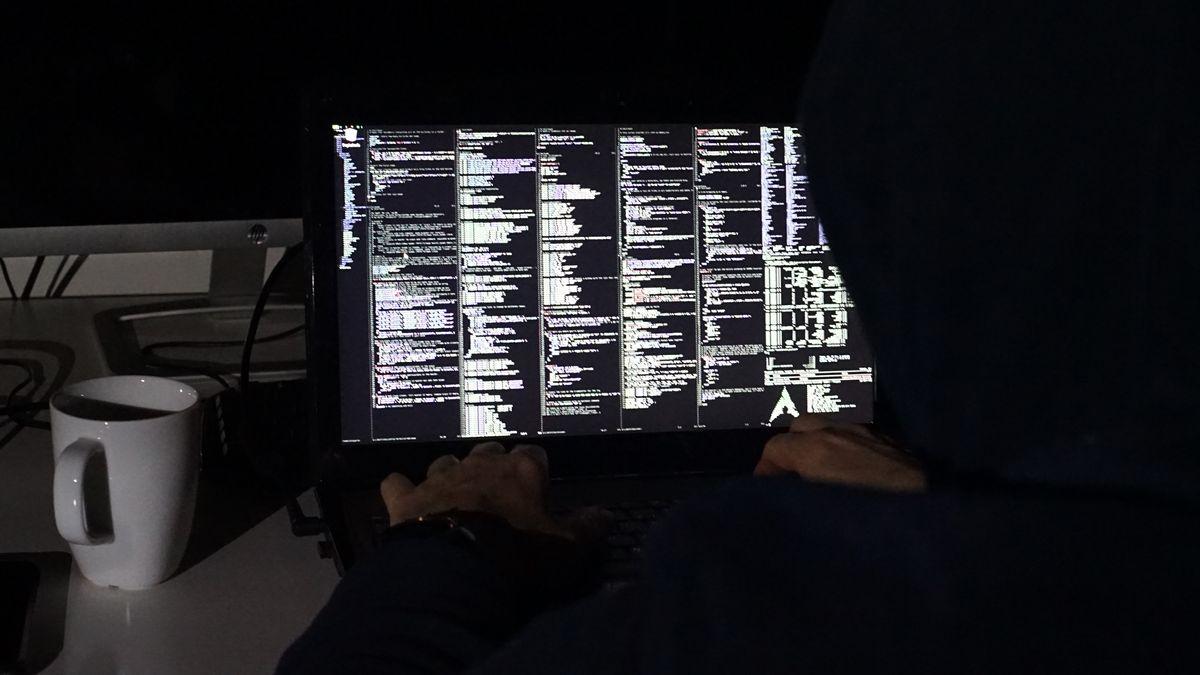 Ein Mann sitzt vor seinem Laptop und schaut sich den Programmcode an.