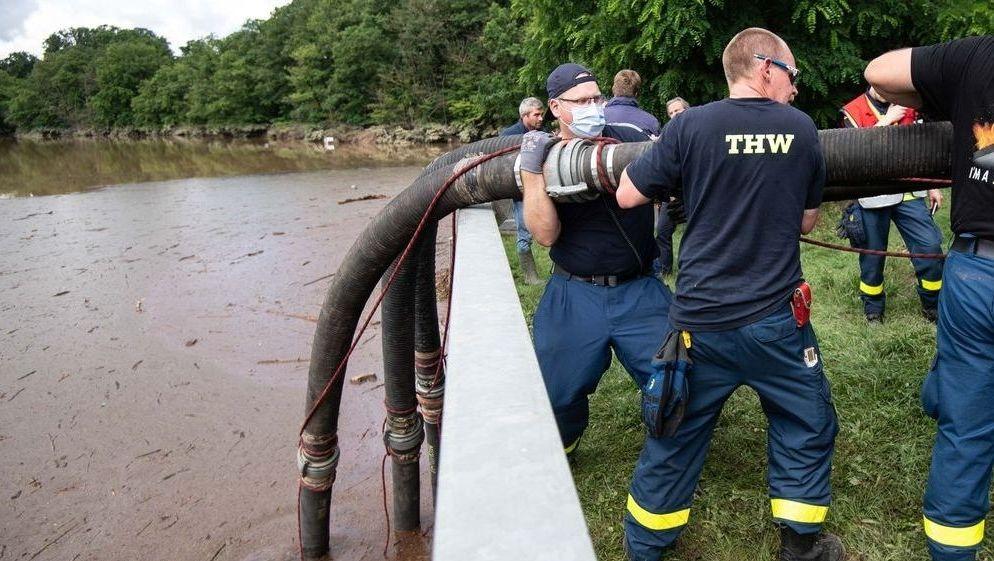 Helfer des Technischen Hilfswerks (THW) lassen Schläuche in die Steinbachtalsperre hinab.