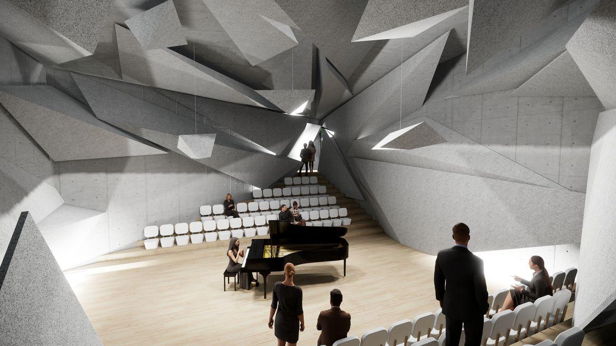Von der Decke eines Konzertsaals hängen graue Gegenstände, die die Akustik verbessern sollen. Darunter steht ein Flügel.