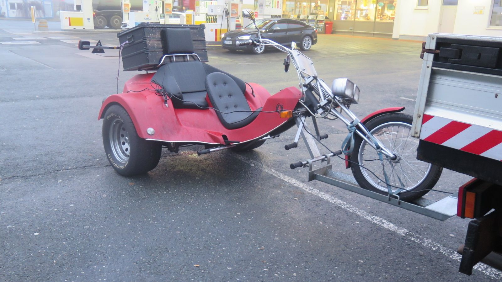 Ein Trike hängt an der Anhängerkupplung eines Kleintransporters.