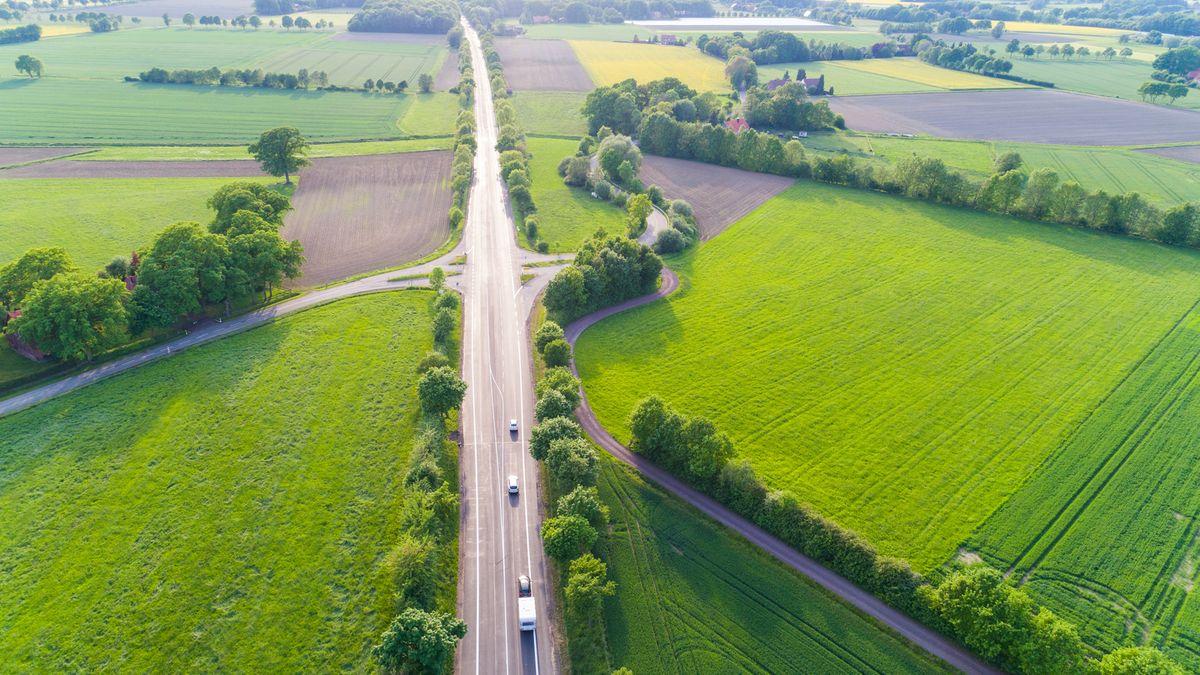 Luftbildaufnahme einer geraden Straße, links und rechts grüne und braune Felder, Baumreihen, Hecken und vereinzelte Häuser. (Symbolbild)