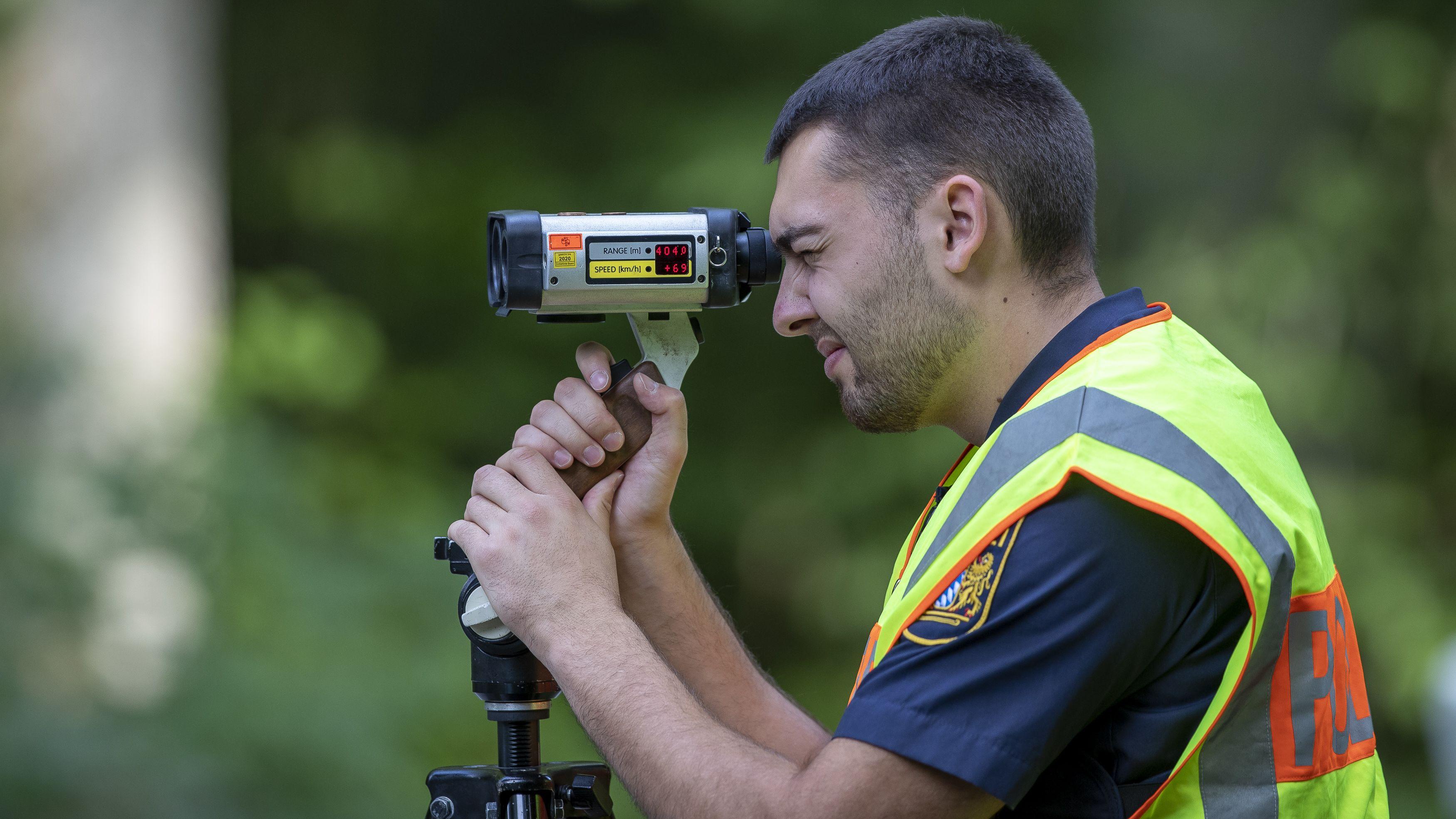 Polizist sieht durch ein Laser-Blitzgerät