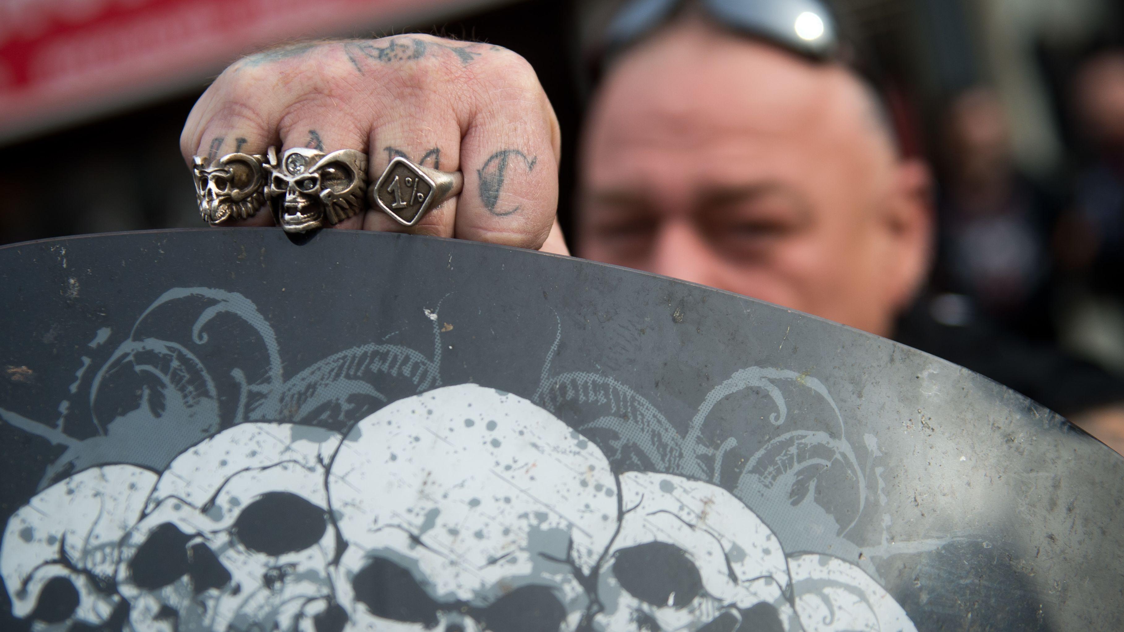 Ein Rocker zeigt Ringe mit Totenköpfen an seiner Hand