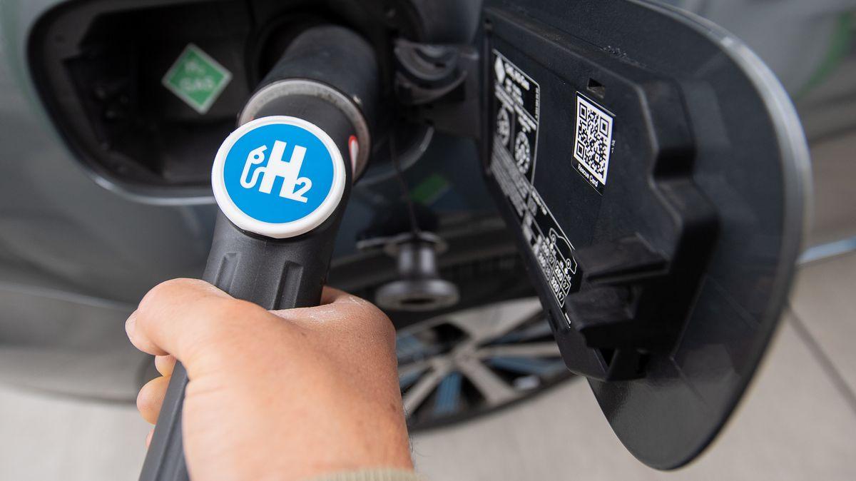 Eine Person tankt Wasserstoff an einer Wasserstofftankstelle.