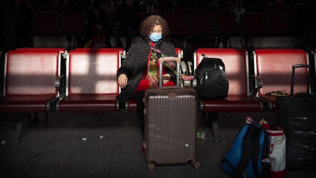 Eine Reisende trägt Mundschutz als Schutzmaßnahme gegen die Verbreitung des Corona-Virus, während sie in einem Warteraum am Pekinger Westbahnhof sitzt.