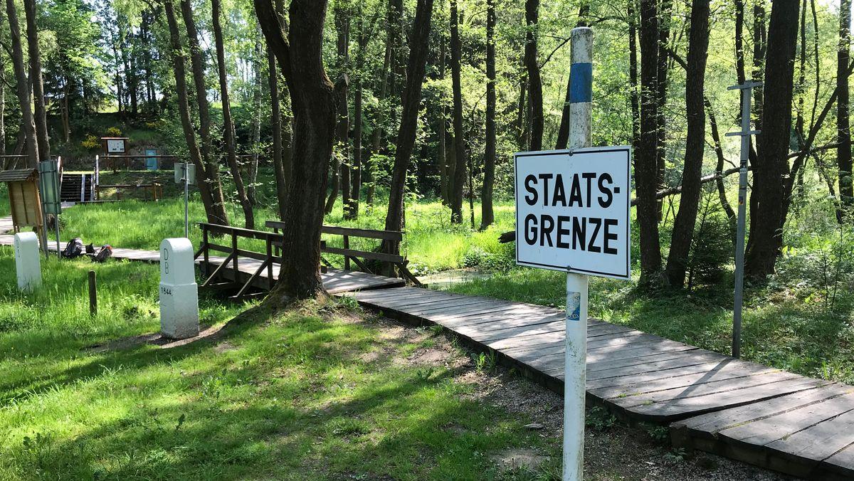 """Ein Schild mit der Aufschrift """"Staatsgrenze"""" steht in der Natur."""