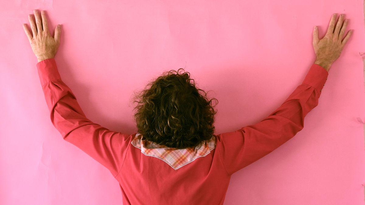 Rückenansicht von Friedemann Weise, in Hände hoch!-Stellung vor pinker Wand