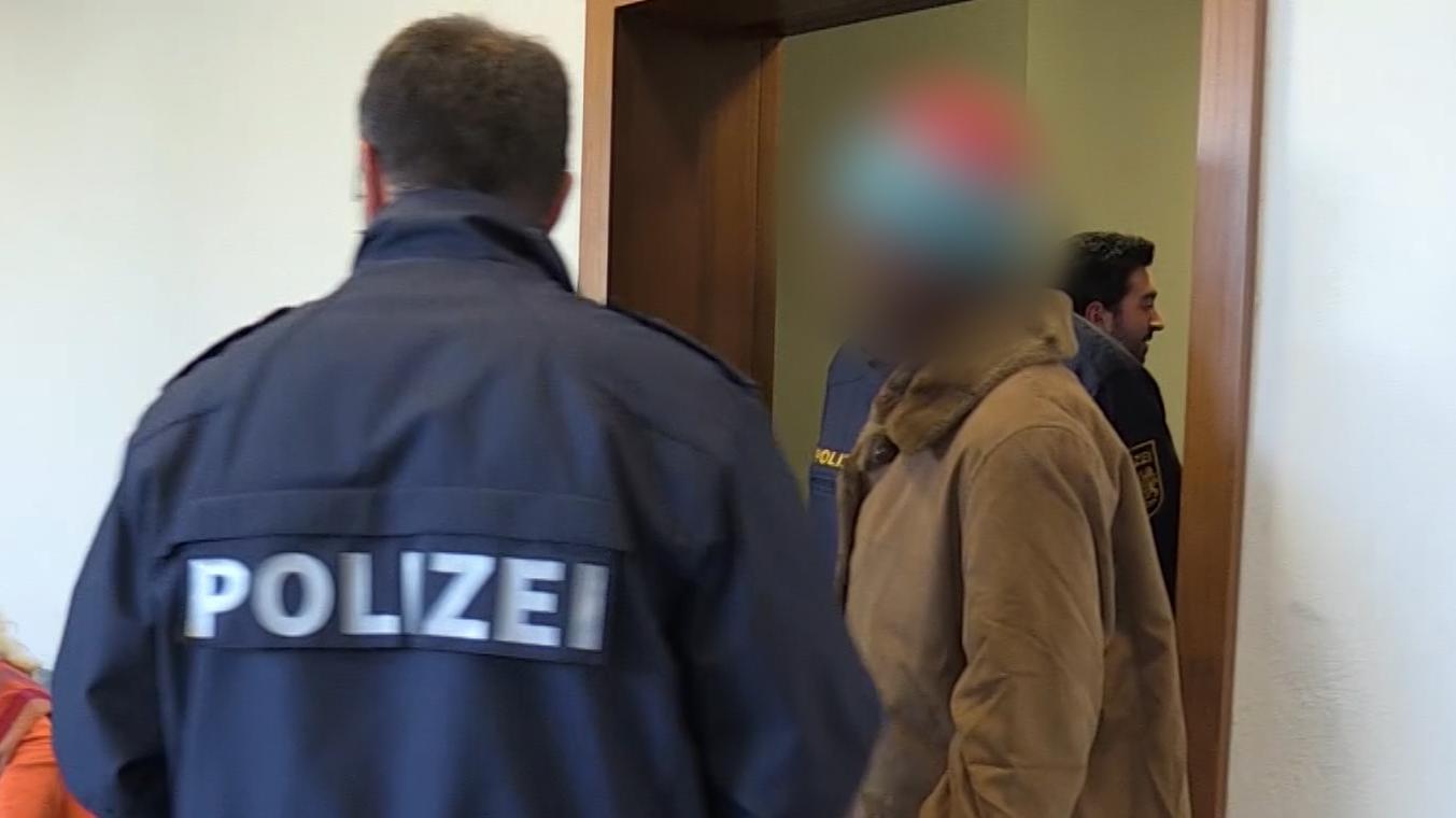 Ein Polizeibeamter begleitet die Angeklagte in den Gerichtssaal.