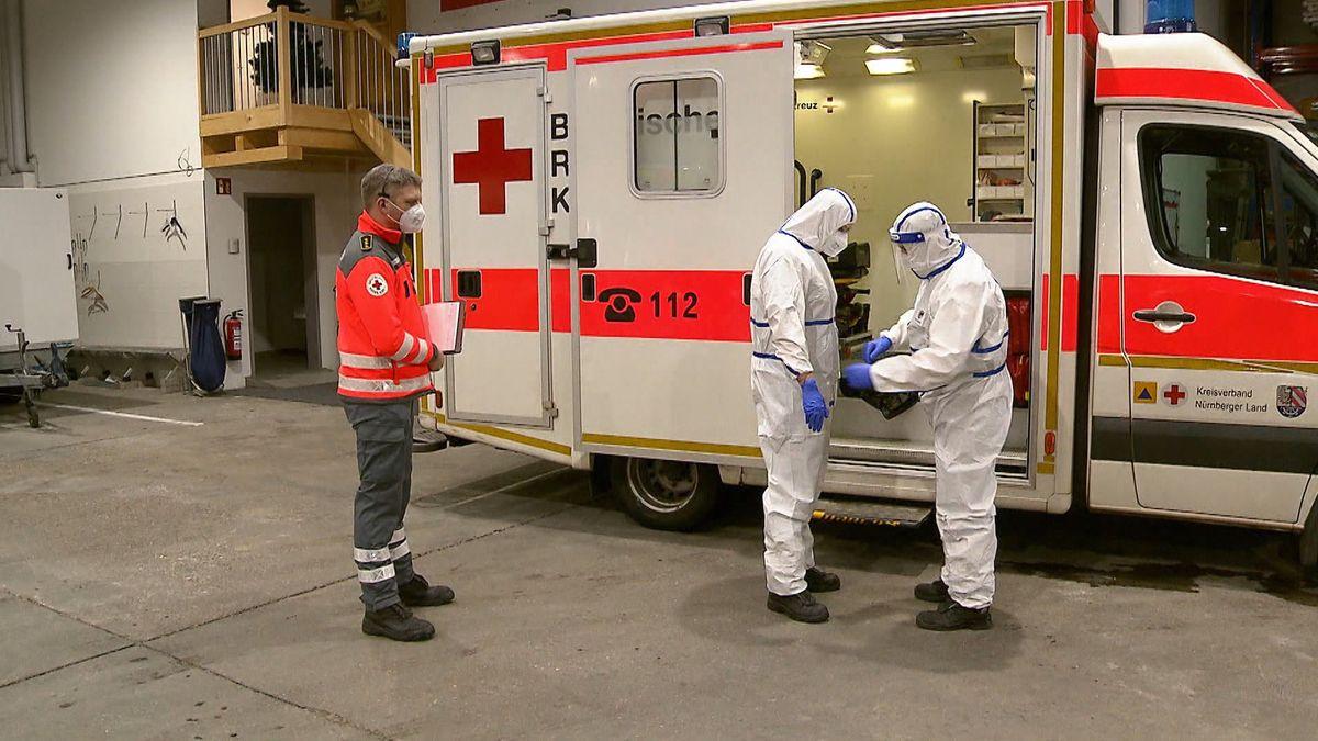 Drei Einsatzkräfte stehen vor eine Rettungswagen
