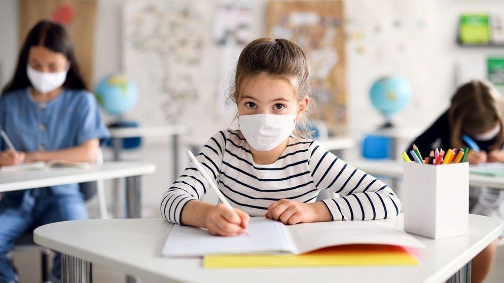 Ein Schulkind mit Maske im Unterricht.