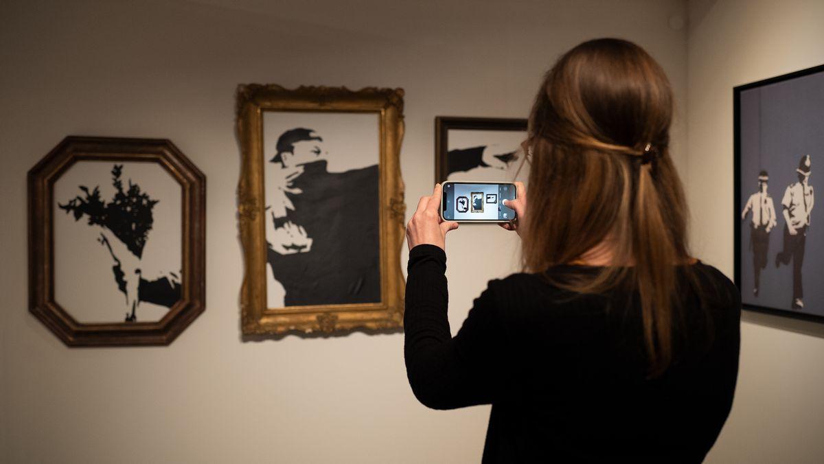 Eine Besucherin fotografiert eine Reproduktion von Banksy.