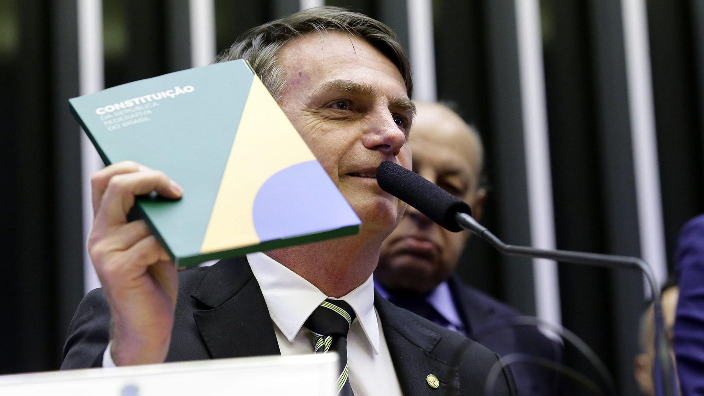 Jair Bolsonaro hält bei seinem ersten Auftritt nach der Wahl die Verfassung hoch. Dabei steht er an einem Mikrofon.