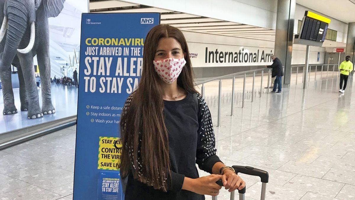 Junge Frau mit Maske am Flughafen.