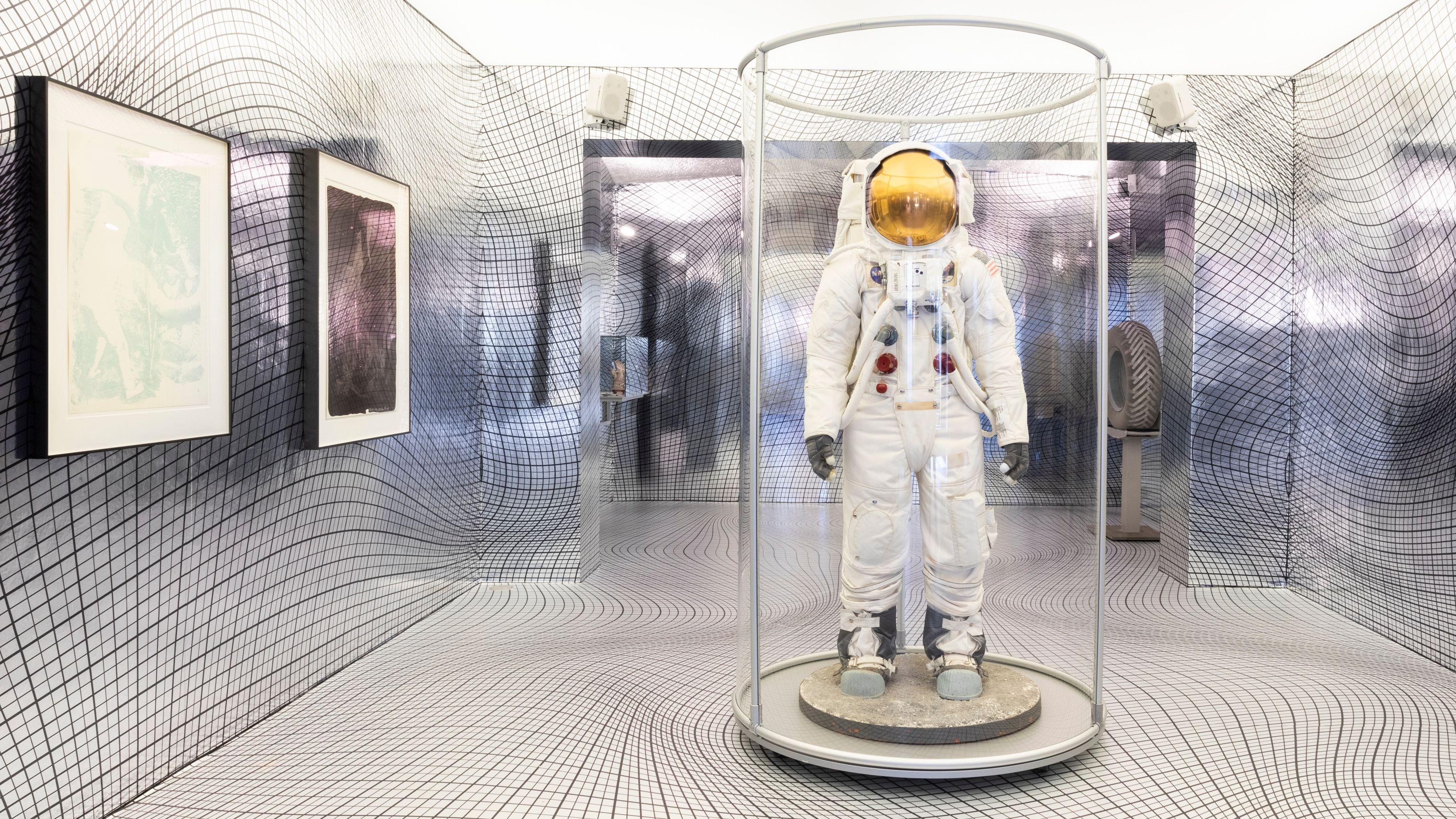"""Ausstellungsraum von """"Zero Gravity"""" mit einer Puppe im Astronautenlook in einer Glasröhre."""