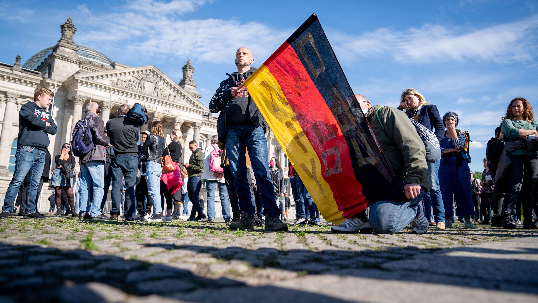 Teilnehmer demonstrieren mit einer Deutschlandfahne vor dem Reichstagsgebäude