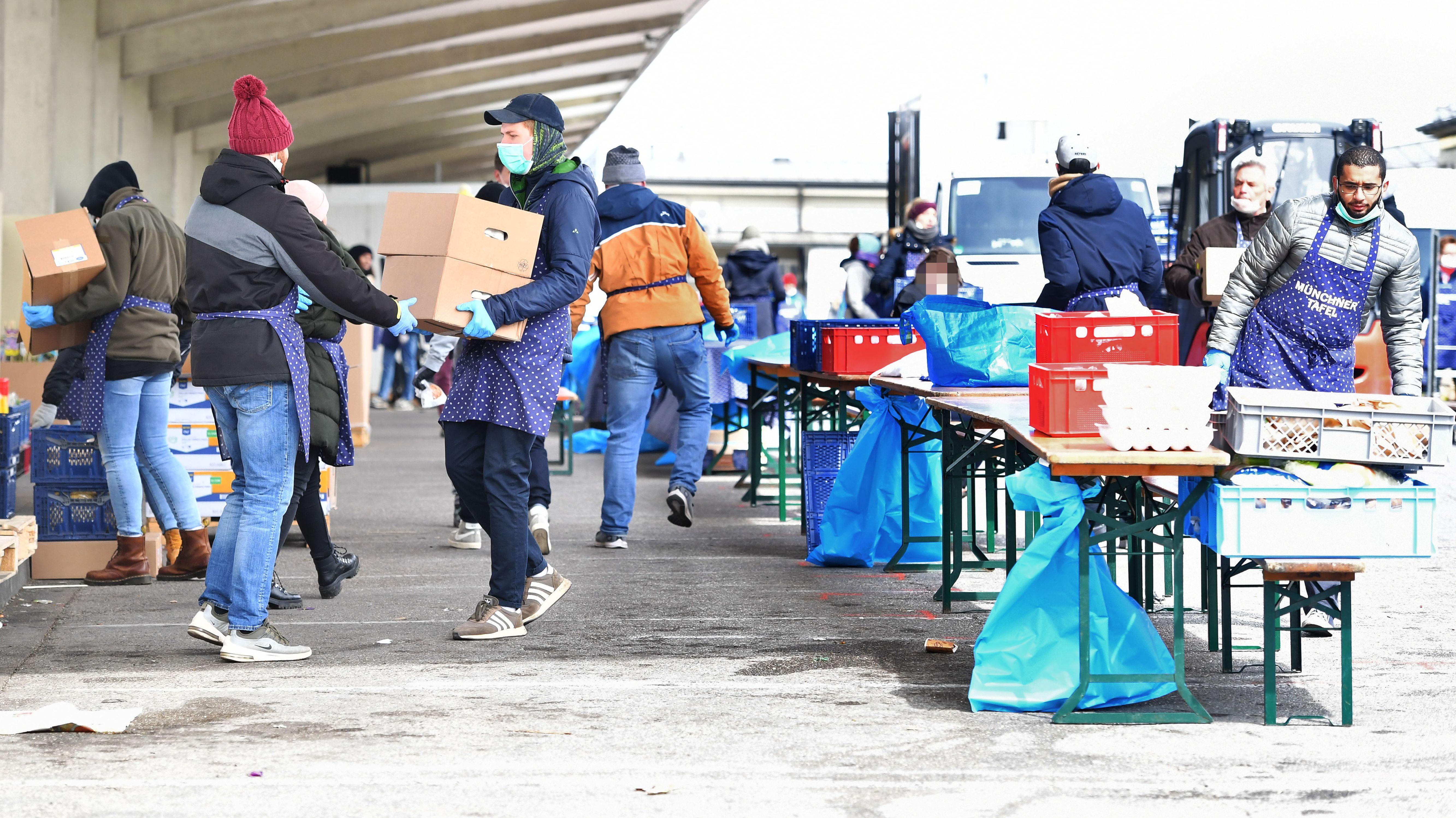 Essensausgabe bei der Münchner Tafel. Helfer mit Mundschutz tragen Kisten mit Lebensmitteln zur Verteilung und Ausgabe an bedürftige Menschen.