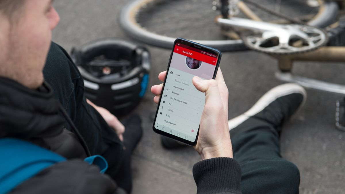 Eine Mann ruft seinen Notfallpass auf dem Smartphone auf nachdem er einen Fahrradunfall hatte