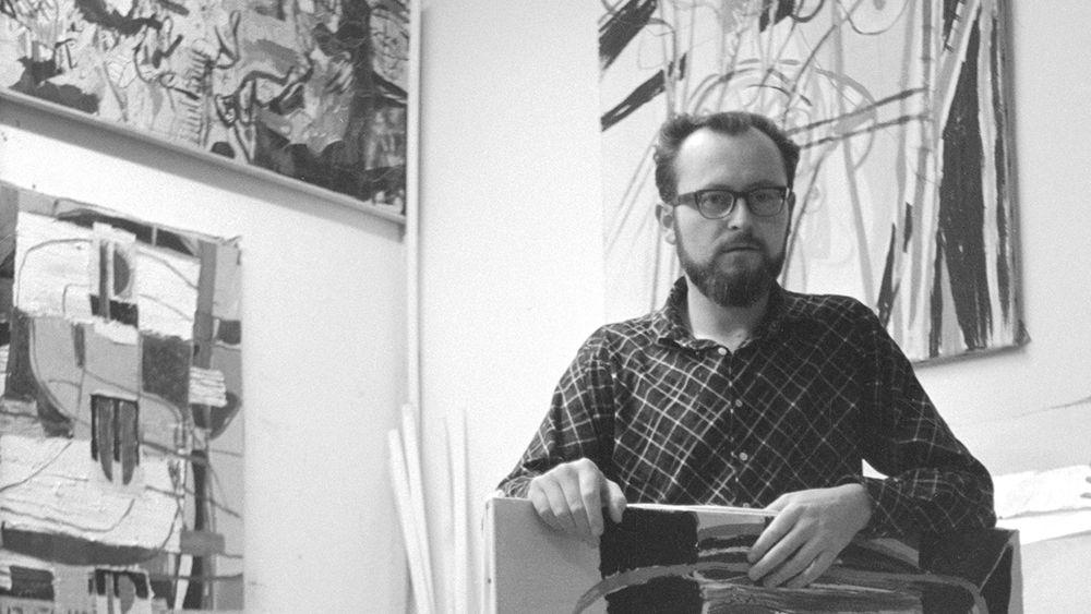 Schwarzweiß-Fotografie eines Mannes mit Bart und Brille mit einem Gemälde in der Hand