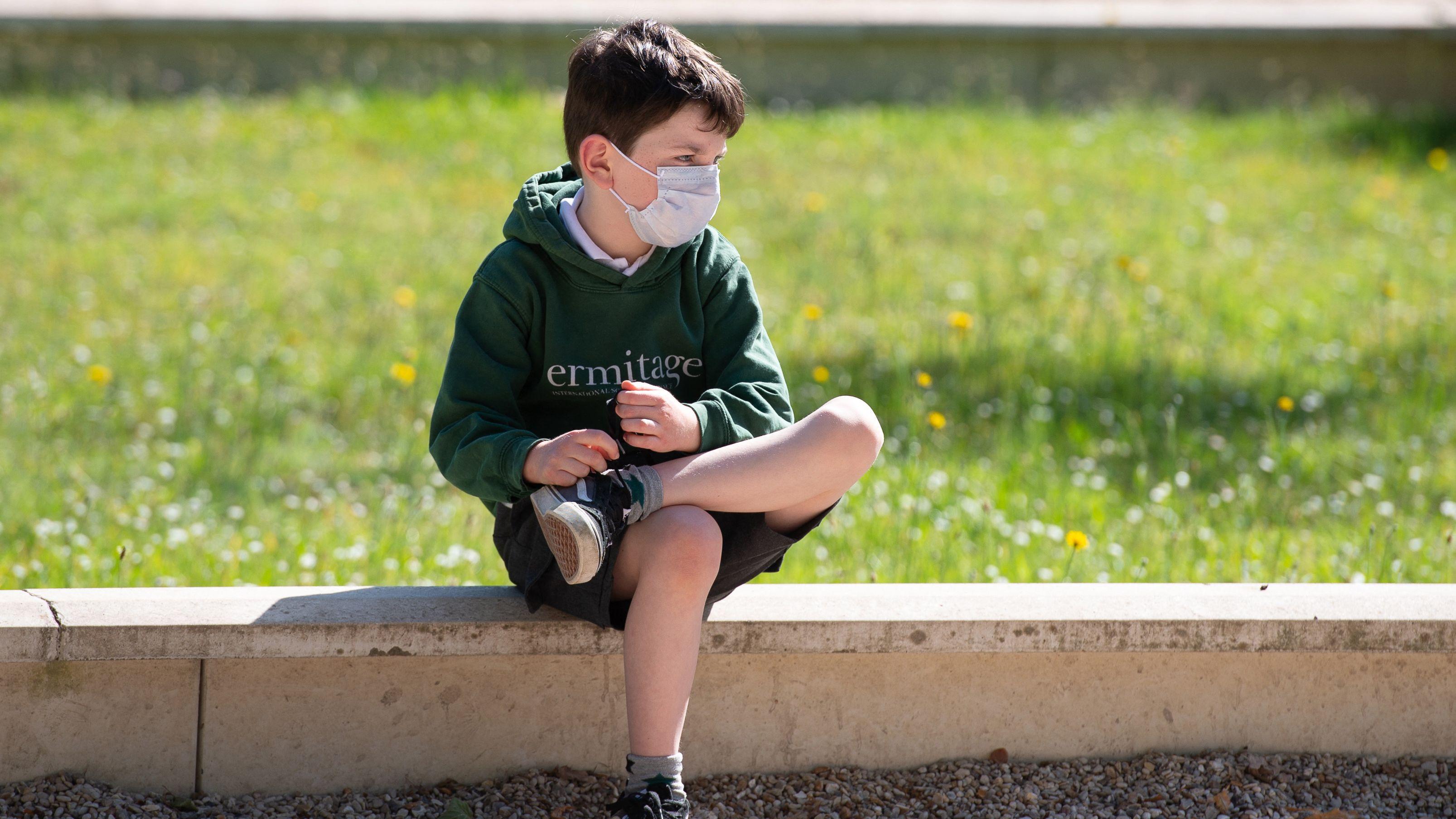 Junge mit Schutzmaske sitzt auf einer Mauer
