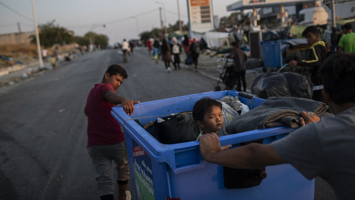Ein Junge zieht einen Müllcontainer, in dem ein Kind sitzt. Migranten gehen in großen Gruppen ins neue Lager von Lesbos