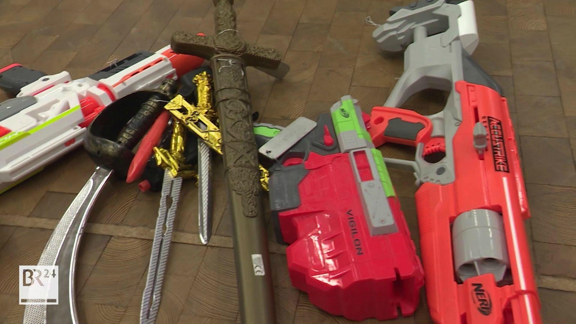 Spielzeugwaffen und Plastikschwerter liegen nebeneinander auf dem Boden