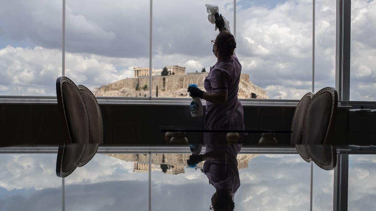 Eine Hotelangestellte putzt die Fensterscheiben in einem in einem Hotel mit Block auf die Akropolis.