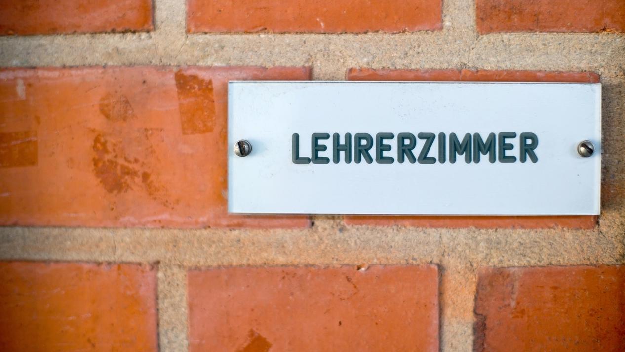 """Das Schild """"Lehrerzimmer"""" ist in einer Schule an einer Wand angebracht."""