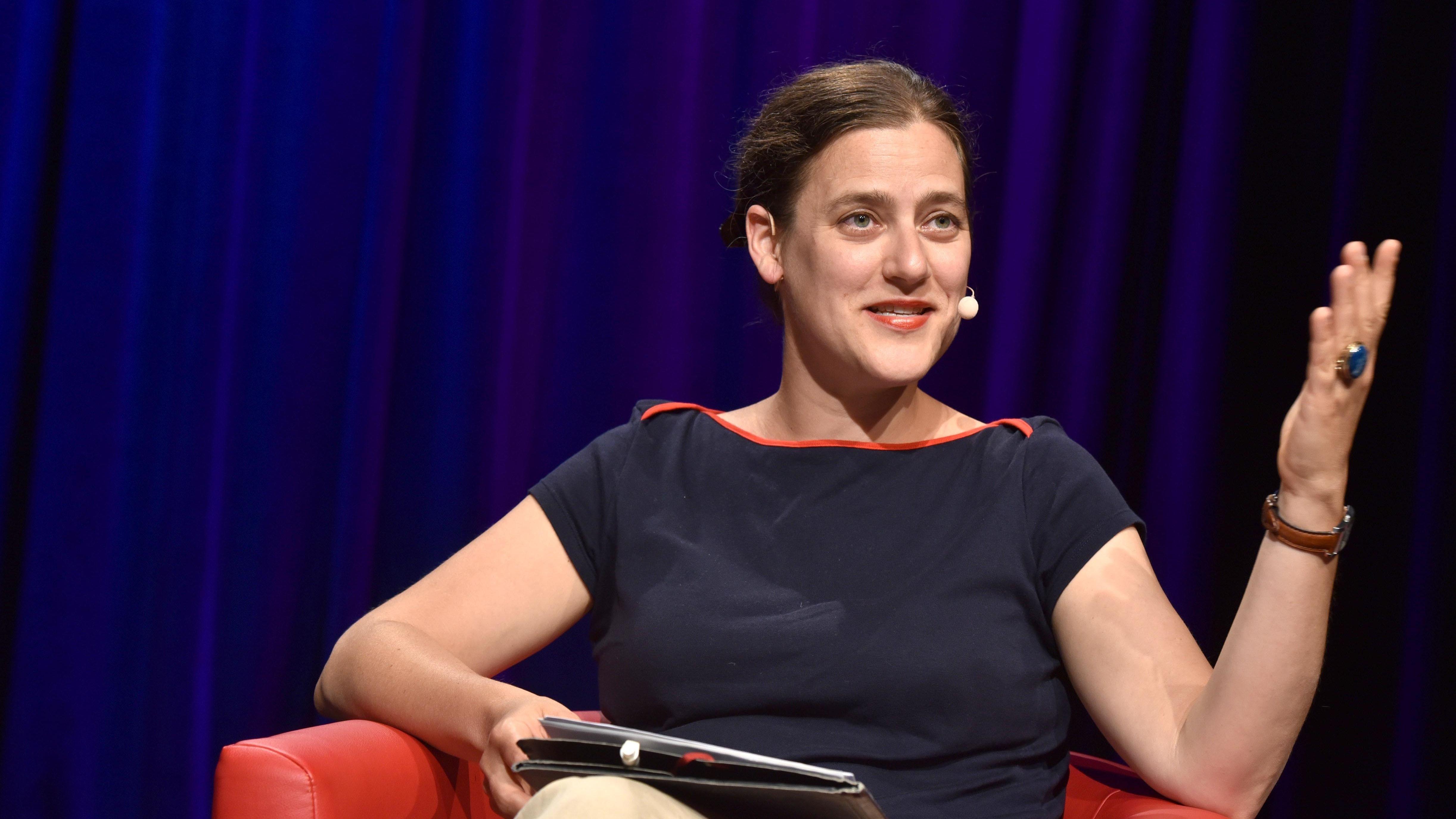 Frau in rotem Sessel, lächelnd gestikulierend: die Schweizer Philosophin Catherine Newmark