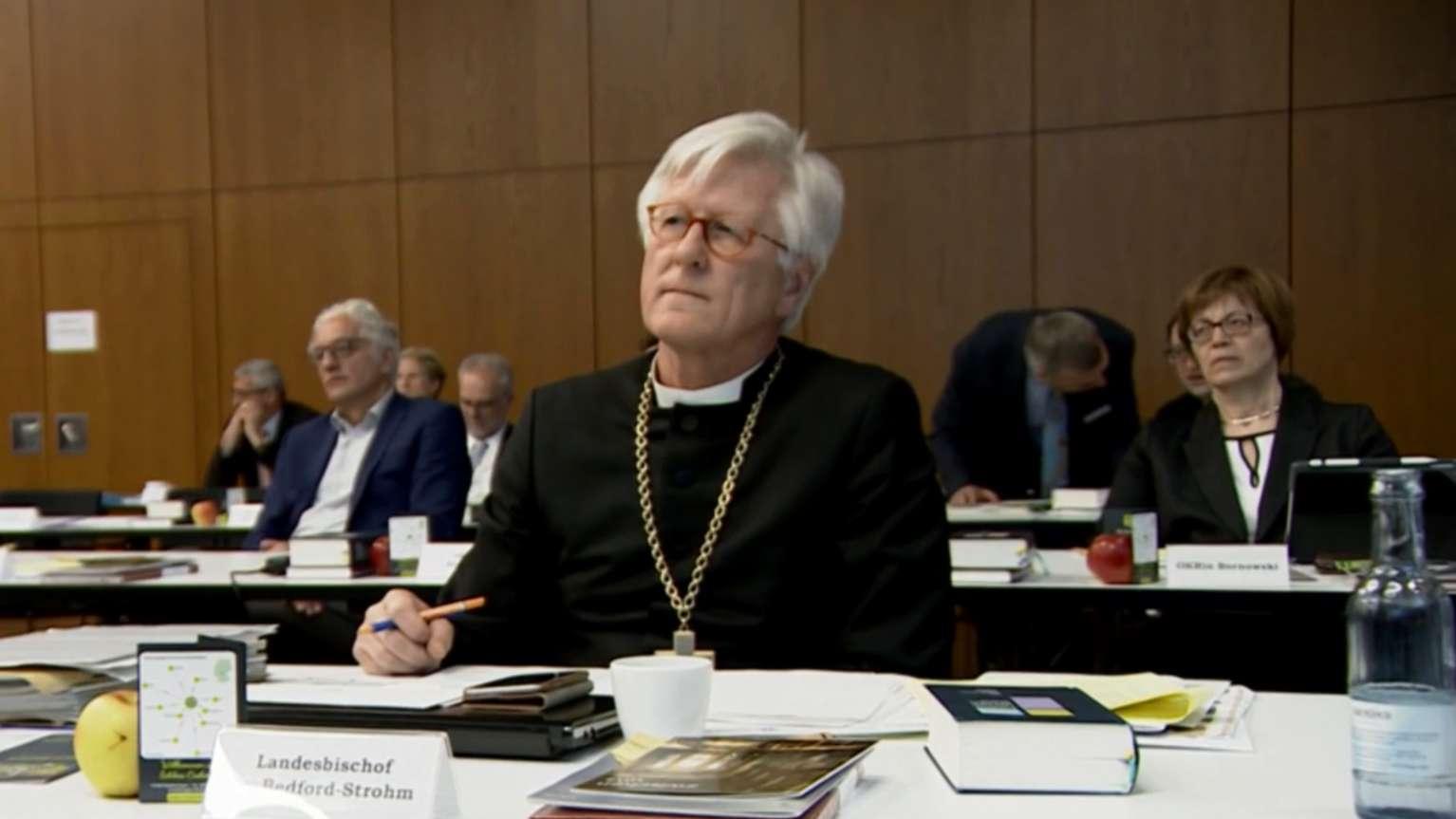 Landesbischof Heinrich-Bedford-Strohm sitzt am Tisch mit bei der Synode in Lindau.