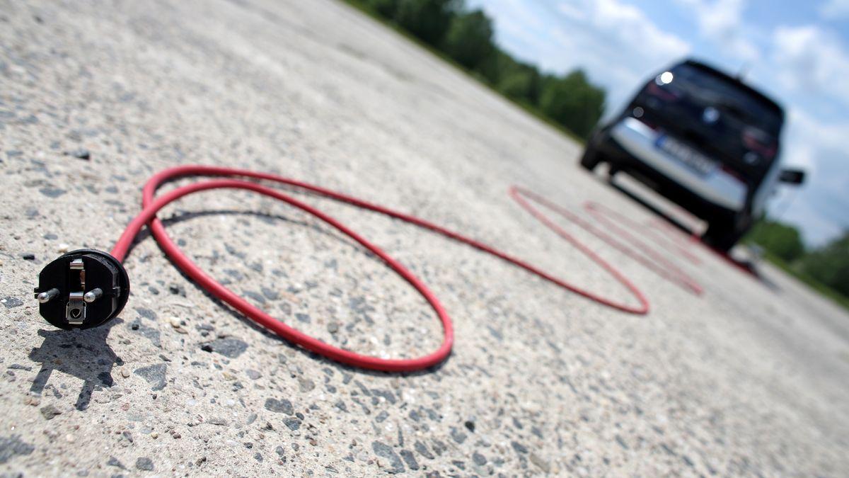 Aus einem unscharf abgebildeten Elektroauto hängt ein Ladekabel mit Stecker.