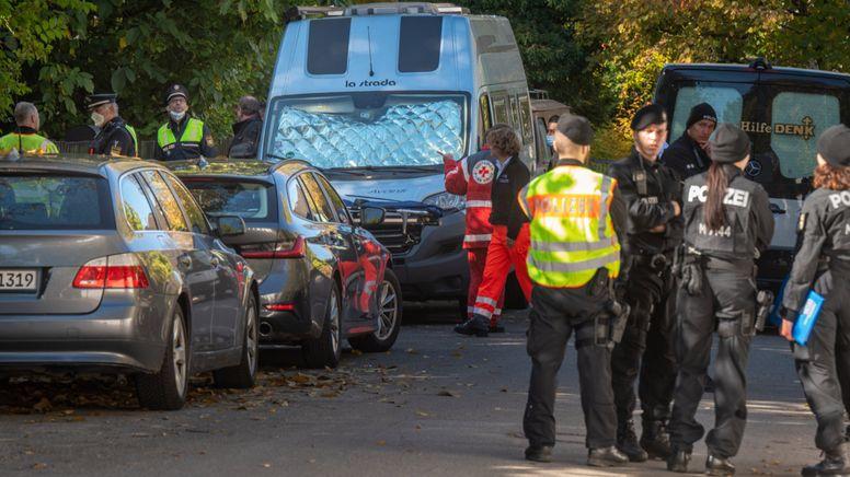 Mitarbeiter des Deutschen Roten Kreuzes und Polizisten stehen vor dem Tatort im Münchner Stadtteil Denning | Bild:dpa-Bildfunk/Peter Kneffel