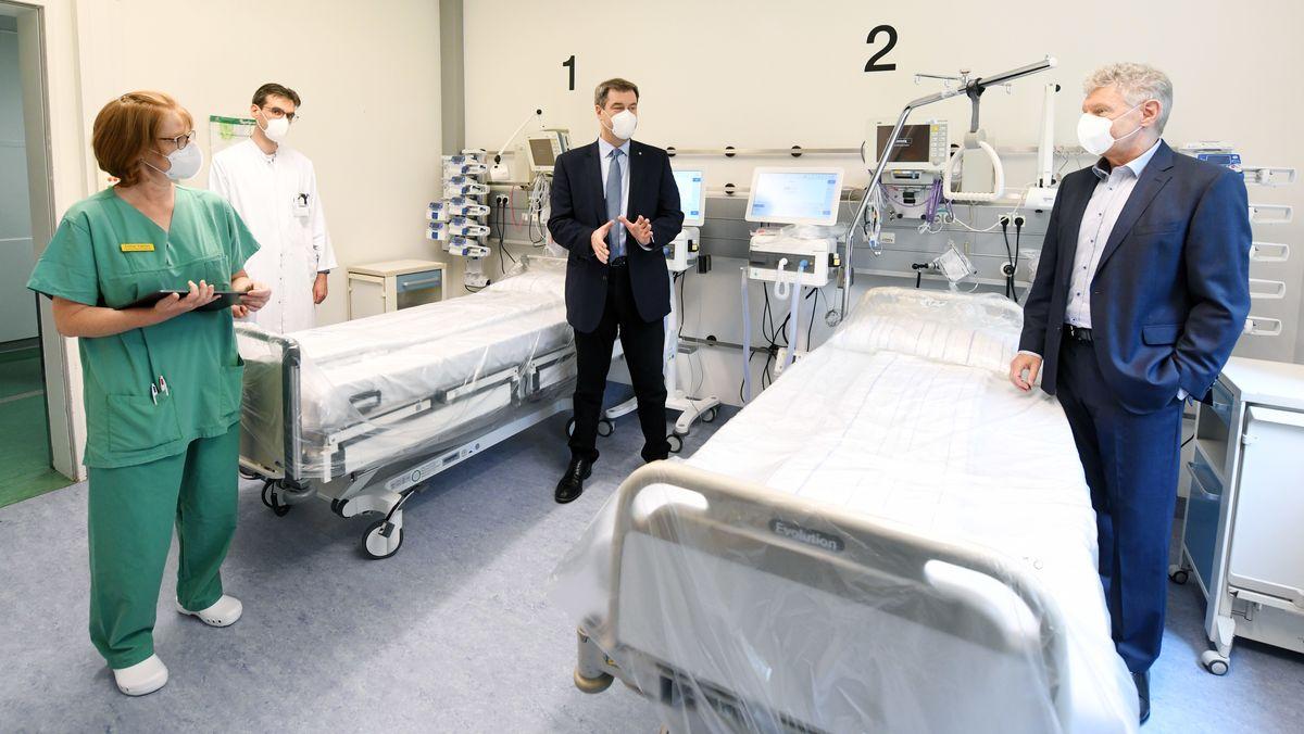 Bayerns Ministerpräsident Söder steht in einem Zimmer der Intensivstation der München Klinik Schwabing und unterhält sich mit einer Pflegerin, einem Arzt und dem Münchner Oberbürgermeister Dieter Reiter