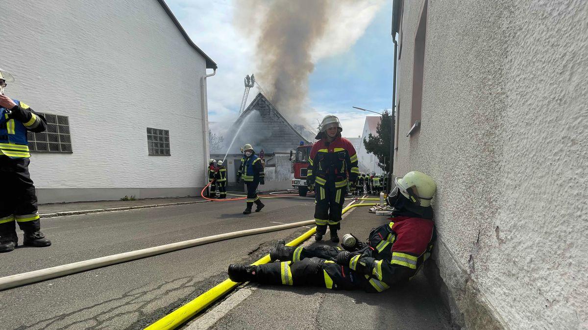 Ein Feuerwehrmann sitzt am Boden, im Hintergrund tritt Rauch von einem brennenden Gebäude auf.