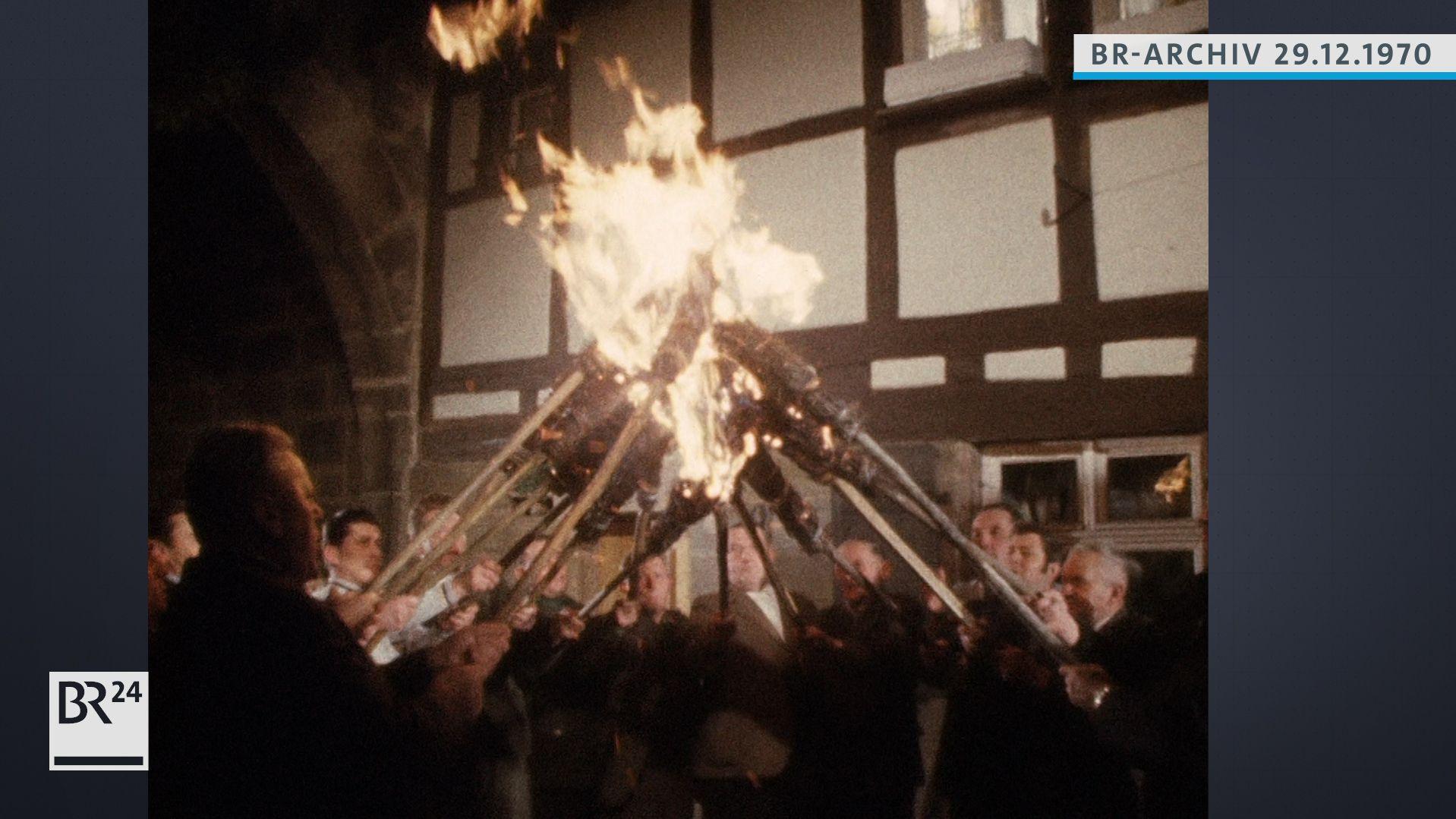 Männer halten brennende Besen in die Luft