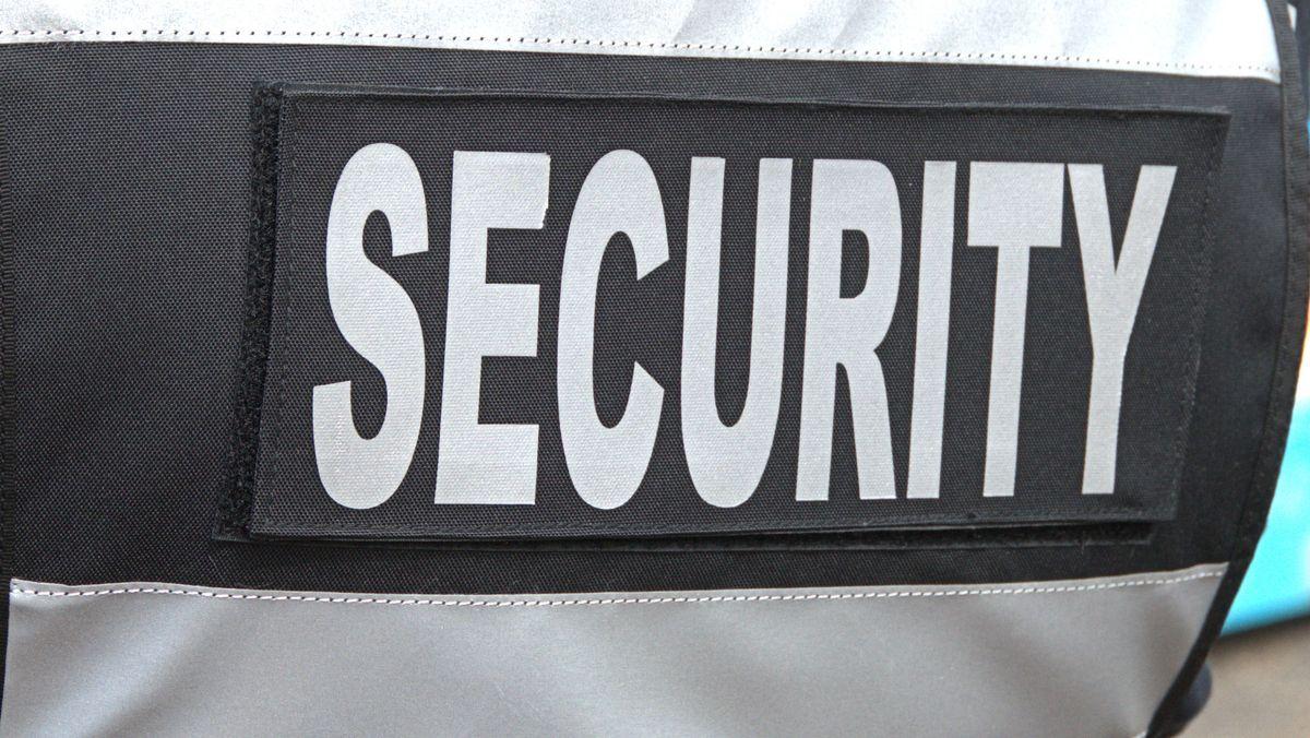 """""""Security"""" steht auf der Jacke eines Sicherheitsdienstmitarbeiters."""